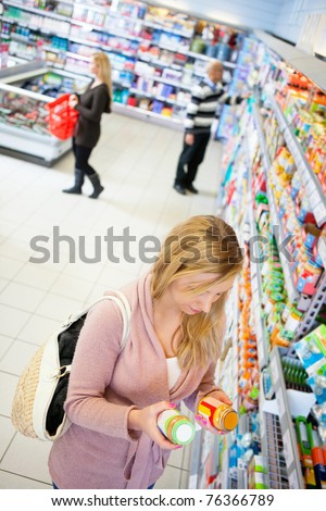 High angle view of a woman comparing products in a grocery store - stock photo