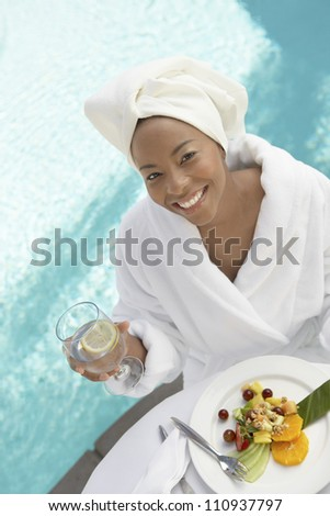 High angle view of a woman having healthy food by swimming pool