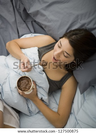High angle view of a woman lying in bed and eating chocolate ice cream