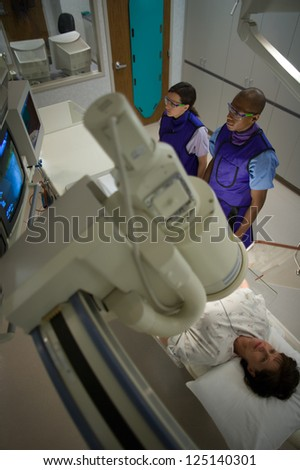 High angle view of a woman undergoing x-ray in lab - stock photo