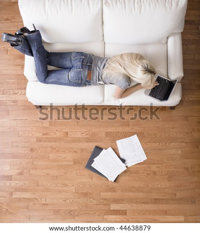 High angle view of a woman using her laptop with papers scattered about. Vertical shot. - stock photo