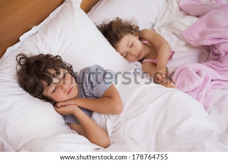 High angle view of a young girl and boy sleeping in bed at home
