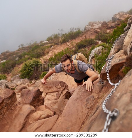 High angle view of a young man climbing up rocks on a nature trail with chains to aid him - stock photo