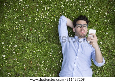 High angle view of a young man using a Smart phone while laying on grass. - stock photo