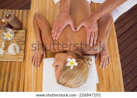 High angle view of a young woman receiving back massage at spa center - stock photo