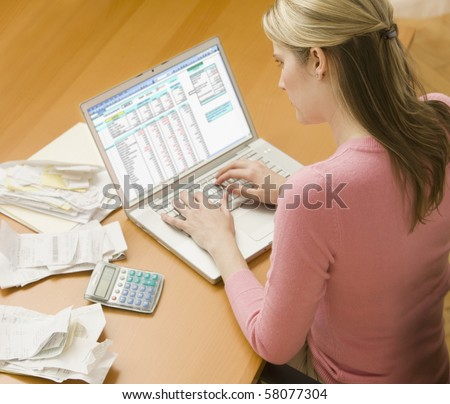 High angle view of a young woman using a laptop computer to organize her finances.  Horizontal shot. - stock photo