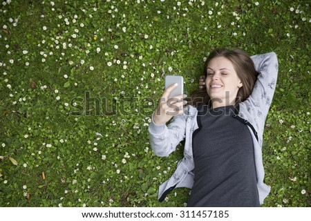 High angle view of a young woman using her Smart phone while laying on grass. - stock photo