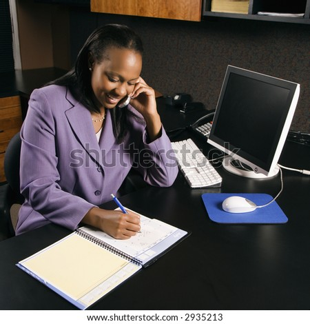 High angle view of African-American young adult business woman talking on cell phone and writing in planner in office. - stock photo