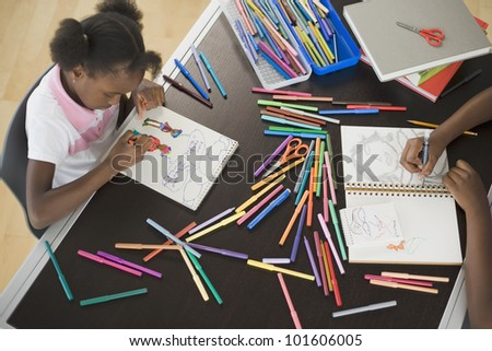 High angle view of African girl coloring - stock photo