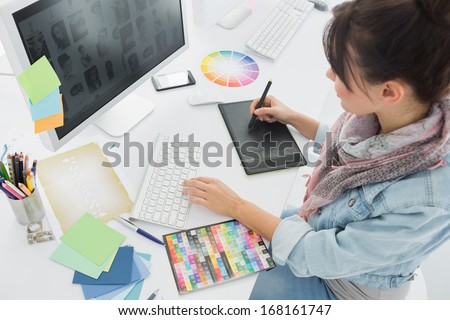 High angle view of an artist drawing something on graphic tablet at the office
