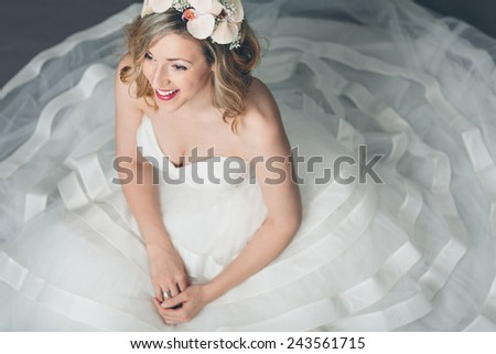 High angle view of an attractive blond elegant young bride in a full skirted white gown sitting on the floor with the fabric spread out round her looking ahead with a happy smile - stock photo