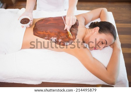 High angle view of an attractive young woman receiving chocolate back mask at spa center - stock photo