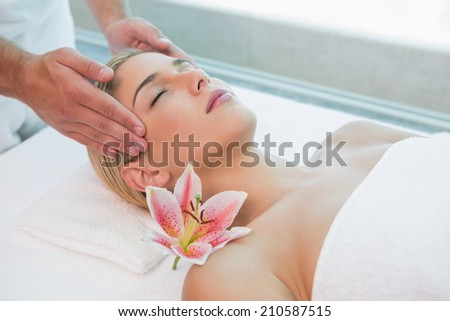 High angle view of an attractive young woman receiving head massage at spa center - stock photo