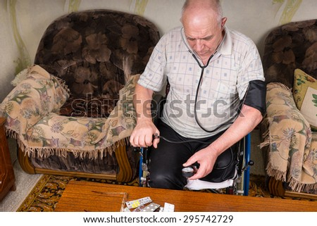 High Angle View of an Elderly Man with Special Needs Sitting on his Wheelchair, Checking his Blood Pressure Using a Manual BP Apparatus inside his House. - stock photo