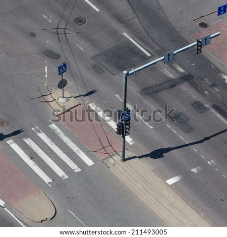 high angle view of an empty street intersection with cross walk markings, traffic signal lights - stock photo