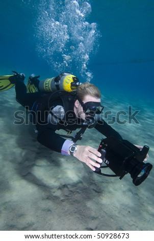 High angle view of an Underwater camerman filming in crystal clear water. MORE INFO: Model released