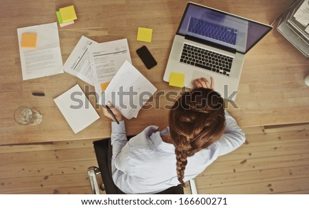 High angle view of an young brunette working at her office desk with documents and laptop. Businesswoman working on paperwork. - stock photo