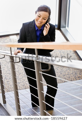 High angle view of Asian businesswoman talking on cell phone and ascending stairs - stock photo