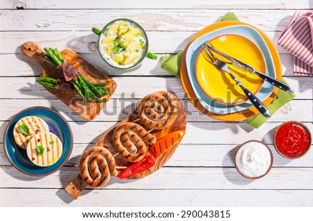 High Angle View of Barbequed Meal of Grilled Sausages and Prepared Side Dishes Arranged on White Picnic Table - stock photo