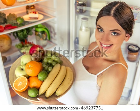 High angle view of beautiful pregnant woman holding a plate of fruits, looking at camera and smiling while standing near the open fridge at home