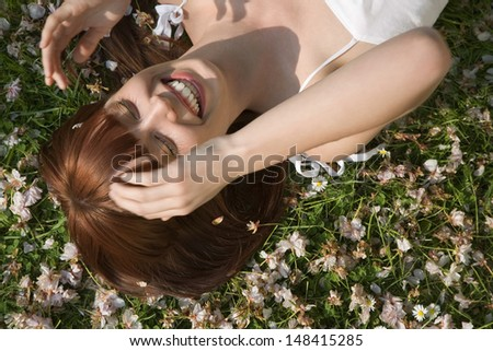 High angle view of beautiful young woman laughing while lying on grass - stock photo