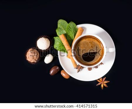 High Angle View of Black Coffee Served in White Cup and Saucer with Fresh Mint Sprig, Cinnamon Stick and Star Anise, on Shiny Black Reflective Surface with Chocolate Covered Coffee Beans and Truffles - stock photo