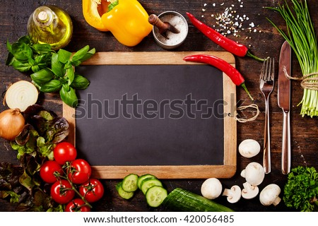 High Angle View of Blank Chalkboard and Silver Knife and Fork Surrounded by Fresh Herbs and Healthy Raw Vegetables Scattered on Rustic Wooden Table Surface