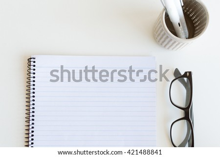 High angle view of blank notepad, glasses and pens in pen holder on white table (cropped) - stock photo