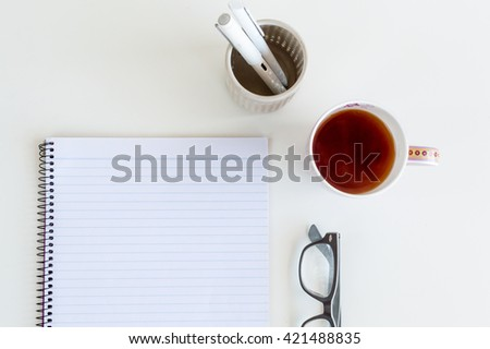 High angle view of blank notepad with cup of tea, glasses and pens in pen holder on white table (cropped) - stock photo