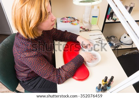 High Angle View of Blond Woman Soaking Hands in Small Bowls of Warm Soapy Water During Spa Manicure Treatment - stock photo