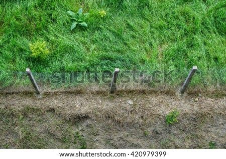 High angle view of border between muddy soil and beautiful green wild grass. Wire fence