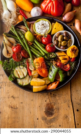 High Angle View of Bounty of Colorful Grilled Vegetables and Olives on Cast Iron Pan Resting on Wooden Table Surface with Copy Space in Foreground - stock photo