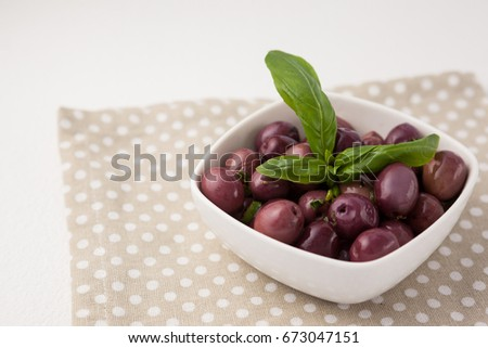 High angle view of brown olives with herb on napkin at table