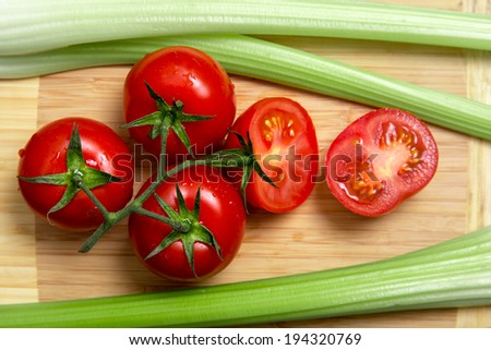 High angle view of bunch of fresh tomatoes and celery sticks on wooden chopping board  - stock photo