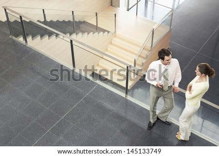 High angle view of business colleagues conversing while standing by railing in office - stock photo
