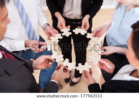 High Angle View Of Business People Assembling Jigsaw Puzzle - stock photo