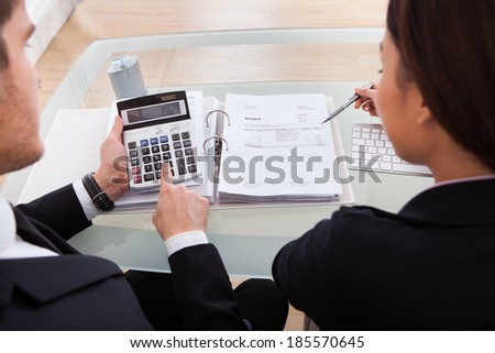 High angle view of business people calculating tax together at desk in office - stock photo