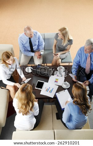 High angle view of business people discussing in a meeting while sitting at conference table. Using digital tablet and computer while analyzing financial data.   - stock photo