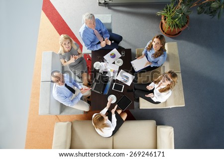 High angle view of business people sitting at meeting. Executive businesswoman presenting her idea to sales team while they are on staff meeting at office. Teamwork.  - stock photo