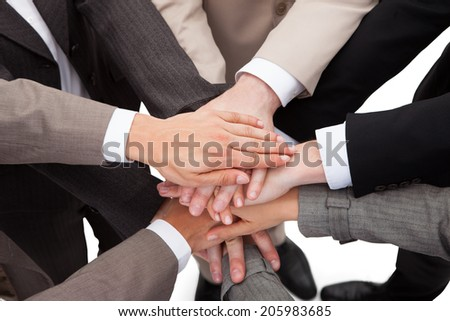 High angle view of business people stacking hands against white background - stock photo