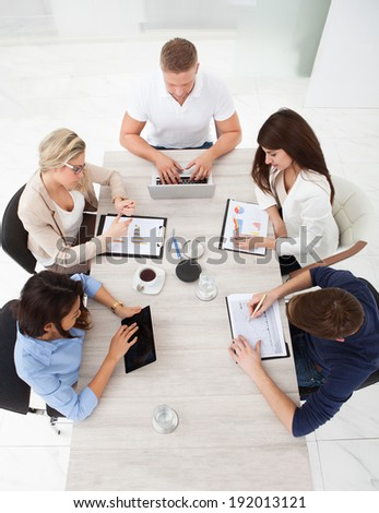 High angle view of business team working at office desk in meeting - stock photo