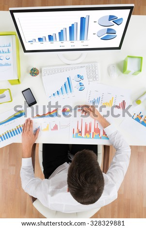 High Angle View Of Businessman Analyzing Graph On Computer At Desk - stock photo