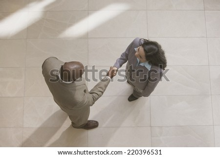High angle view of businessman and businesswoman shaking hands