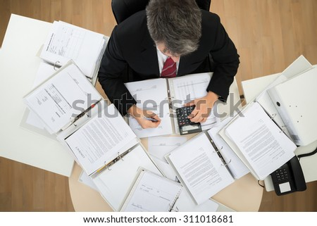 High Angle View Of Businessman Calculating Invoices At Office Desk - stock photo