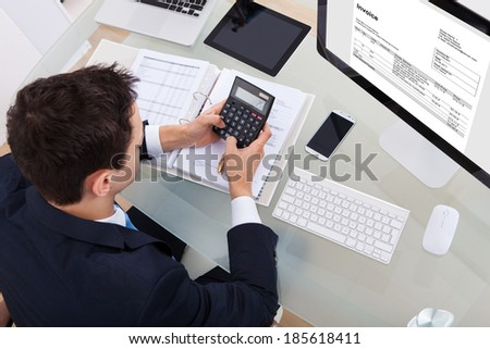 High angle view of businessman calculating tax at desk in office - stock photo