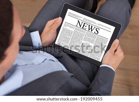 High angle view of businessman reading news on digital tablet in office - stock photo