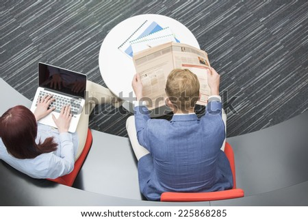 High angle view of businessman reading newspaper while female colleague using laptop in office - stock photo