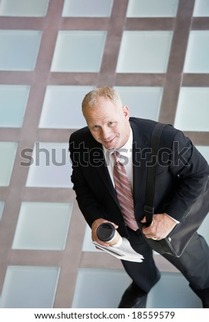 High angle view of businessman standing with briefcase and coffee in the morning - stock photo