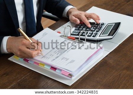 High angle view of businessman using calculator while checking invoice at desk