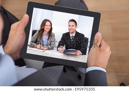 High angle view of businessman video conferencing with colleagues on digital tablet in office - stock photo